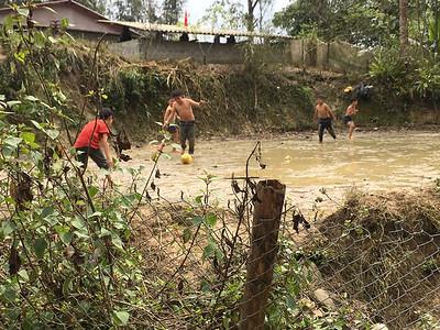 Children playing soccer an a muddy field