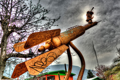 This sculpture was in the school yard close to the Plaza in San Jose de Maipo, Chile. Couldn't find out who the sculptor is, in spite of a number of attempts on Google, etc. Apparently his trademark signature is the man with the looking glass, which he puts on all his work. It was a very cloudy day, so the HDR effect really made the clouds look dramatic.