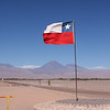 Entrance to the Valle de la Luna park in San Pedro with the Chilean flag flying and the Licancabur volcano in the background