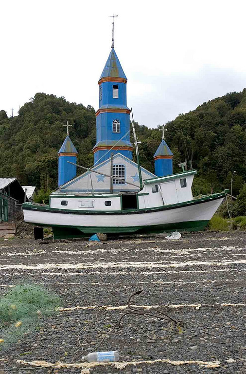 Church with boat beign painted in front of it.