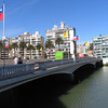 The Chilean national flag flying on a lovely bridge over a tidal canal.