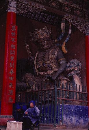 Old woman being stared down by a Buddhist statue in a temple! (I'm not actually sure which temple we saw this in)
