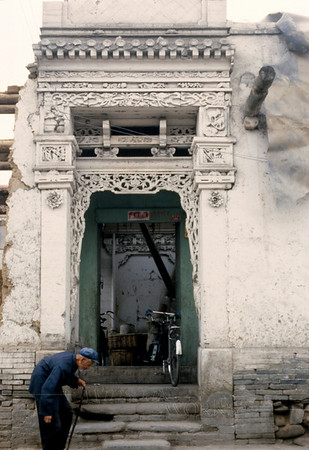 Old man and intricate doorway in Lanzhou, Gansu Province
