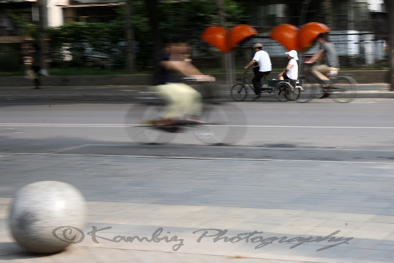 young man carrying a mid age woman on his bicycle, Beijing, China