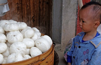 Around Yangshou: Fuli village. This kid was utterly transfixed by the basket of hot dumplings.