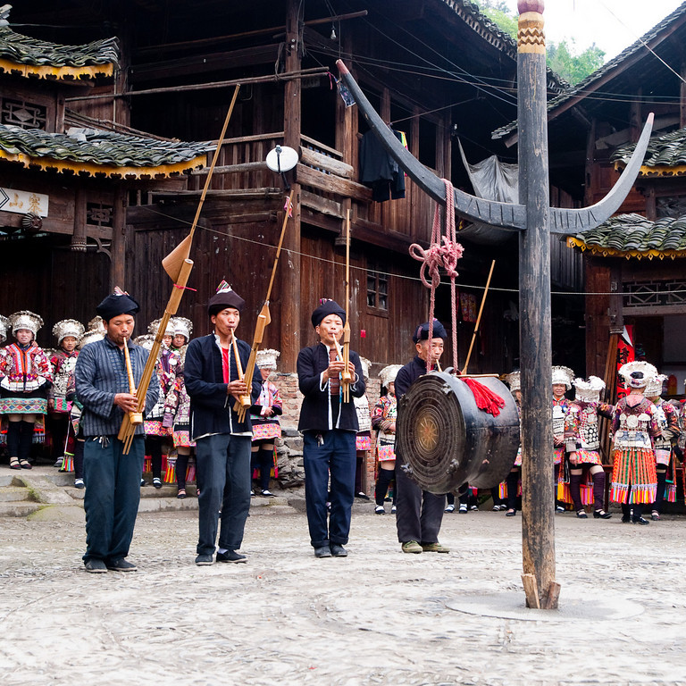 """Traditional May festival at Da'tang. At this festival the performers were really enjoying themselves (at 11 am on a damp morning... it must have been all that the rice wine !). <br /> In this tiny village 'square' (it was round!) hemmed in by 2-3 story wooden houses, there were about 75 brightly dressed 'performers' having a whale of a time in a well choreographed series of dances ........ and singing too!. They don't do it for free, the village gets about 800yuan but the five of us had at least 45 minutes of great entertainment, and when they had finished....... they came out again and practiced some new dances. (lots more pictures in the China 2010 > Da'tang gallery or at <a href=""""http://agbr.smugmug.com/Travel/China-2010/Datang/12356730_tDH2R#882935441_wRGcz"""">http://agbr.smugmug.com/Travel/China-2010/Datang/12356730_tDH2R#882935441_wRGcz</a>)"""