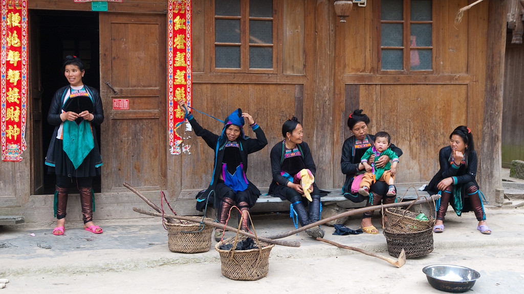 Dong Women sit outside their houses in  Yintan... their calves are bound with a cloth that is dyed with indigo. It has an amazing sheen. More on the processes involved in its production in >Guizhou Cloth.