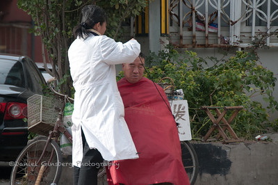 Getting a haircut on the street in Beijing, China.