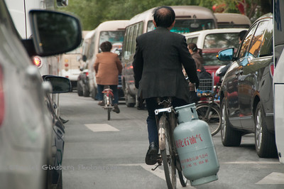 Beijing bicyclist carrying propane tank.