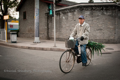 Bicyclist carrying green vegetables.
