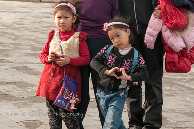 Girl making a heart sign with her hands at the Temple of Heaven.