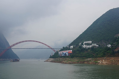 Wushan Yangtze River Bridge in Chongqing Municipality, China.  Wushan Yangtze River Bridge 巫山长江大桥 Wushan, Chongqing, China 590 feet high / 180 meters high 1,509 foot span / 460 meter span 2005  Source: http://highestbridges.com/wiki/index.php?title=Wushan_Yangtze_River_Bridge  The Wushan Yangtze River Bridge is an arch bridge, which crosses the Yangtze River near Wushan, Chongqing, China. Completed in 2005, the 130 metres (430 ft) high arch spans 460 metres (1,510 ft) ranking it in the top ten longest arch bridges in the world.[1] The bridge is also among the highest in the world however, the reservoir created by the construction of the Three Gorges Dam has increased the height of the water below the bridge, and the full 180 metres (590 ft) clearance is no longer visible.  Source: http://en.wikipedia.org/wiki/Wushan_Yangtze_River_Bridge  One of the largest and most spectacular arch bridges ever built, the Wushan Yangtze River bridge is the second crossing of the 3 Gorges reservoir upstream of the massive dam. A gateway to the city of Wushan, millions of visitors a year pass under the bridge as they travel up through the famous 3 Gorges region of the Yangtze River. A half through arch with a main span of 1,509 feet (460 meters), Wushan ranks 7th among the world's longest span arch bridges. The main arch was constructed using the stayed cantilever method whereby a tower is erected on either side of the gorge and cables temporarily radiate out from it to support individual sections of the arch until the two halves can be joined in the middle. A cable high line between the tops of the two towers was used to move the steel sections into place high above the river. Once the arch was closed, concrete was pumped into the 8 main ribs of the arch span, stiffening and strengthening the entire structure. If you are traveling through the 3 Gorges region, I highly recommend you visit the bridge by disembarking your boat at the dock in Wushan and hiring a taxi driver to take you to the bridge. Plan on a one hour round trip drive to the bridge plus another hour to photograph it and take a stroll across. Just be sure to get back to the dock in time for the last boat! A beautiful scene of the bridge being lit up at night can be seen in the excellent 2005 Chinese movie Still Life which chronicles a man's journey to find his wife. Photographed in and around the cities of Wushan and Fengjie when they were being rebuilt to accommodate the rising reservoir, the film has a slow, lingering pace that captures a world that is sometimes so real it seems almost surreal. It won the Golden Lion award at the Venice Film festival. It is available for rental on Netflix.  Source: http://highestbridges.com/wiki/index.php?title=Wushan_Yangtze_River_Bridge
