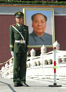 Beijing - Chinese Guard and large portrait of Chairman Mao at the gateway to the Forbidden City at Tiananmen Square.