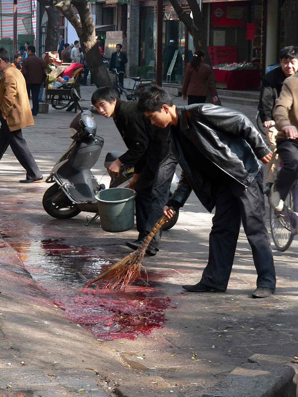 I think (or HOPE!) they are cleaning up pommegranit juice...although it does look like blood.