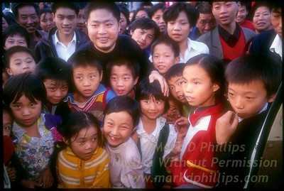 "Children gather at doorway of van as Jay Cochrane arrives at school in Fengjie, China, to board helicopter for start of the ""Great China Skywalk."""