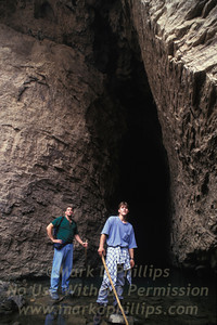 Steve Sless and Clinton Randall stand by a cave entrance on the Yangtze River bank in Qutang Gorge, China. This cave is now 500-feet under water in the lake formed by the Three Gorges Dam.