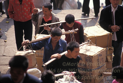 Workmen carry goods through the streets of Fengjie, China in 1995.
