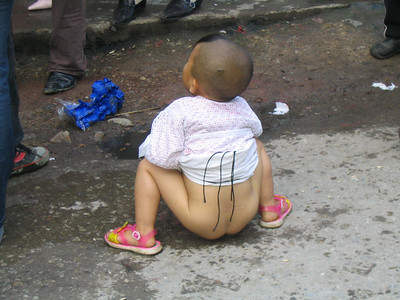Peeing in the steet.  Why not.  She them drops her walnut into the puddle of pee and picks it right up.