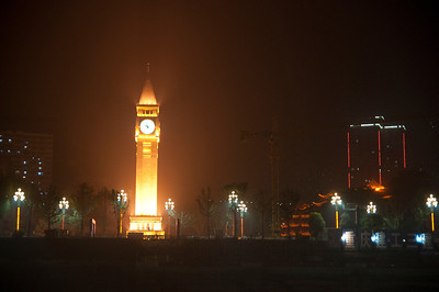 Clock tower lit up at night along the Yangtze River.