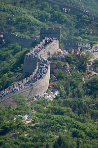 Hundreds of tourists walking and climbing the Great Wall of China at Badaling Hills.  In the heat of the day, the uneven path of the wall can be a very strenuous climb.