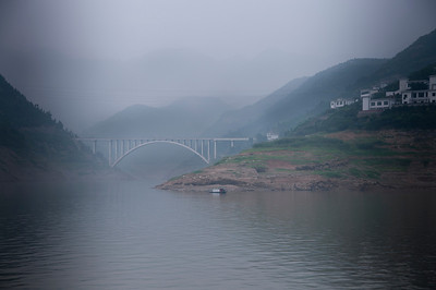 Early morning view of a bridge enveloped in the mist and fog along the Yangtze River.