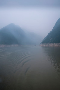 Smaller boats can barely be seen when entering the Lesser Three Gorges on the Daning River.  A series of limestone ridges barely visible in this scene coming off of the well known Yangtze River.