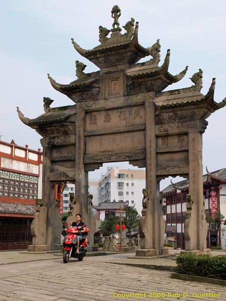 Woman on scooter under arch. Historic Gate Arches in Old Village. Longchang, Sichuan Province, P. R. China. China Trip 30 Aug to 07 Sep 2008.