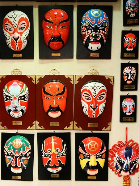 papier mache' masks in a store window.