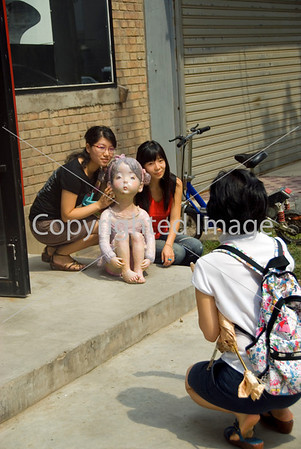 Beijing, CHINA-  Chinese Teenagers Visiting in Art District 798 in Chaoyang Disrtict, Females Posing for Photos with Contemporary Sculpture Outside Art Gallery. Directphoto