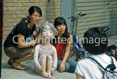 Beijing, CHINA-  Chinese Teenqgers Visiting in Art District 798 in Chaoyang Disrtict, Females Posing for Photos with Contemporary Sculpture outside Art Gallery.  http://www.worldofstock.com/closeups/TAP1096.php Directphoto
