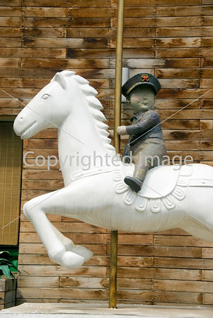 Beijing, CHINA-  Chinese Contemporary Sculpture of Red Army Guard on Merry-go-Round on Display Outside Art Gallery in Art District 798 in Chaoyang District  http://www.worldofstock.com/closeups/TAP1098.php Directphoto