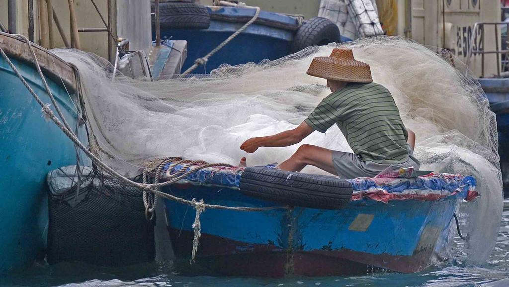 Fisherman mending nets in Hong Kong.
