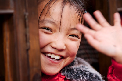 A young girl gives me a smile and a wave.
