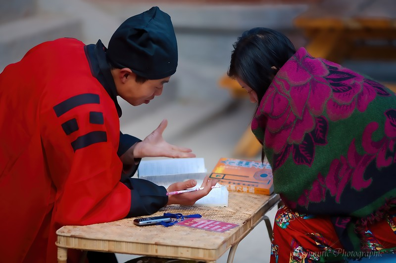 A fortune teller reviews his findings with a young woman.