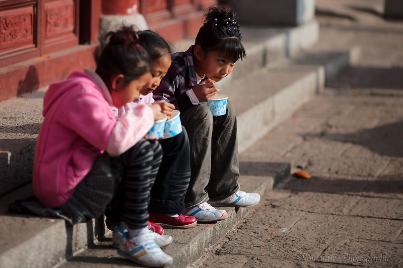 Three kids enjoy a quick lunch of instant noodles.