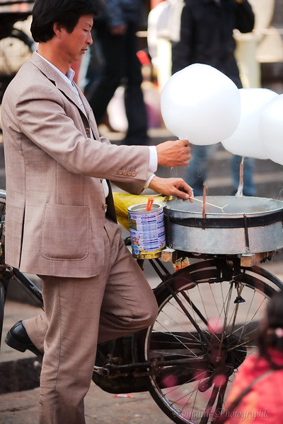 A very well-attired fellow produces cotton candy using bicycle power.