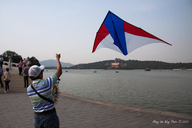 China-1506<br /> Man flying kite on the Seventeen Arch Bridge in the Summer Palace in Beijing, China.