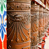 "Prayer wheels, or mani wheels, are large drums inside which are scrolls of Tibetan Buddhist prayers wrapped tightly around the center axle. Tibetan Buddhist practitioners believe that each turn of the prayer wheel is equivalent to them having said those prayers. Saying the scripted prayers earns them merit that will improve their status or situation in their next lives. Mani wheels are elaborately carved with Tibetan Buddhist symbols, including religious instruments and deities, as well as mantras. The ones here are carved with the six-syllable ""Mani Mantra"", one of the most commonly known and recited among the laity."