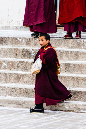 A young monk carrying snacks.