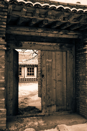 A doorway offers a glimpse into a layperson's or monk's residential courtyard.