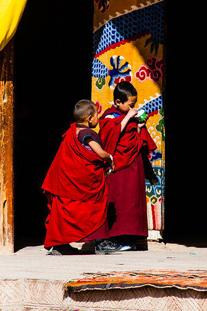 Two child monks enjoy some ice cream before the cham dance starts.