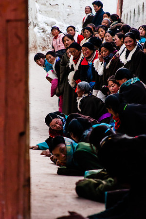 Tibetans prostrate themselves in front of the cham performers to gain blessings.