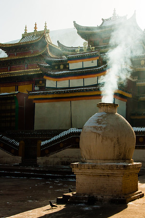 Aromatic smoke from burning tsampa and incense fill the air.