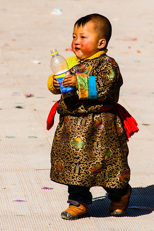 A Tibetan child, dressed in a modern-style chuba, happily holding a bottle of Pepsi.