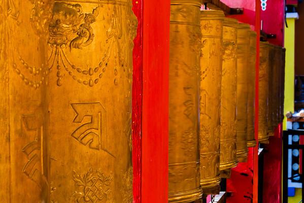 Spinning prayer wheels at the bottom of Upper Wutu Monastery's chorten.