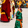 A brave Tibetan girl risks the monks' admonishments in wandering within the Cham dance circle for a better view.