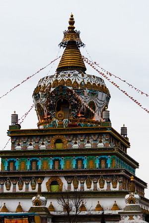 At dusk, yak butter lamps light the top of the chorten.