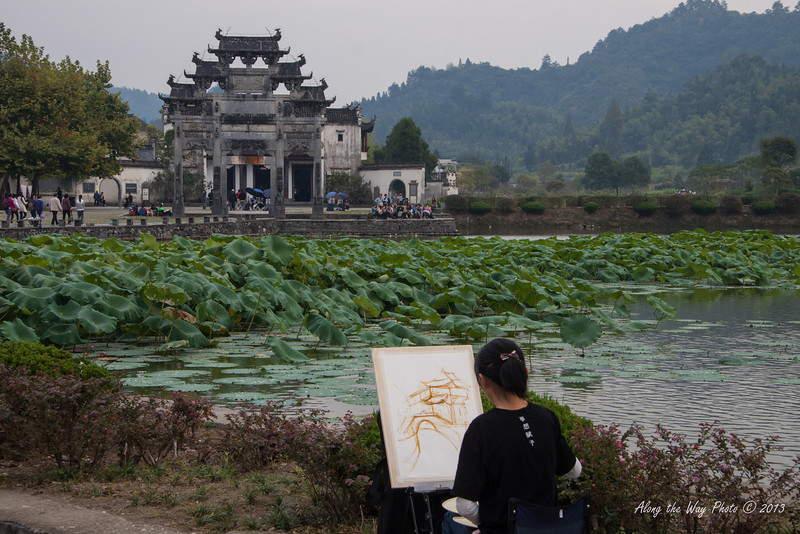 China-3466<br /> Artist sitting by the pond painting entrance of old city gate to Xidi Village.
