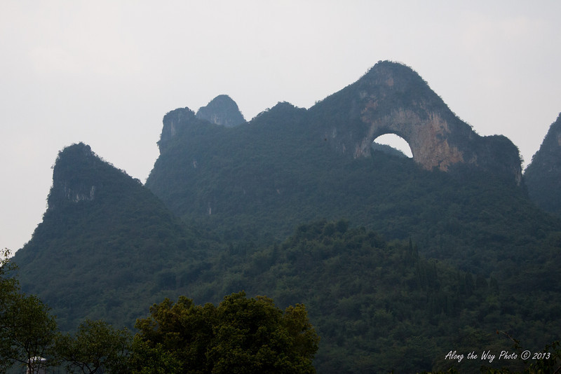 China-2617<br /> Moon hill is a Karst Formation just outside of Fenglou Village by the Yulong river. It is 1248 feet hight, 1345 feet long and 721 feet wide with a hole in the middle.