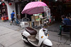 China-3294<br /> Some of the Motor scooter will have umbrellas to protect the  rider from sun and rain. In the small towns and cities the umbrellas are used on the scooters at slower  traffic speeds.